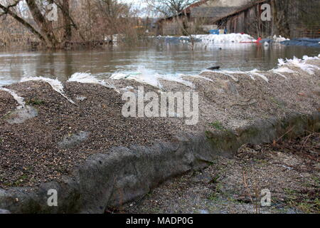 Old sandbags flood protection completely destroyed at top holding back strong river with trees, branches and flood protection in background - Stock Photo