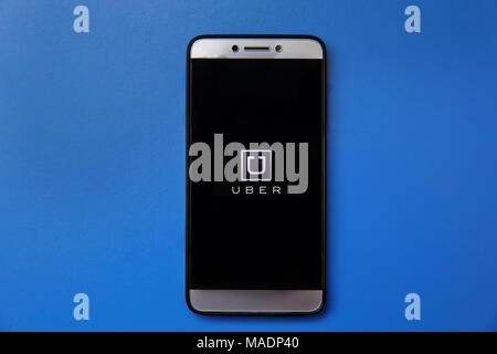 Uber logo on smartphone screen on blue background. - Stock Photo