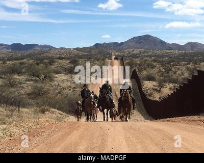 U.S. Secretary of the Interior Ryan Zinke, center, rides horseback with U.S. Border Patrol Tucson Sector Chief Patrol Agent Rodolfo Karisch, right, along the U.S.- Mexico border in the Buenos Aires National Wildlife Refuge March 17, 2018 near Sasabe, Arizona. Zinke visited the border to assess border security and interagency collaboration with U.S. Customs and Border Protection. - Stock Photo