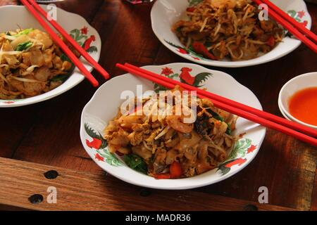 Fried Kway Teow, a popular street food dish of stir-fried flat rice noodles with seafood, vegetables and soy sauce in Medan, North Sumatra. - Stock Photo