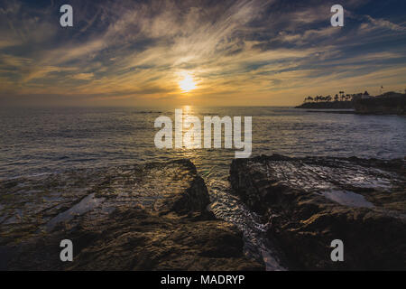 Beautiful coastal view of a colorful sky at sunset with waves crashing into rock formations and water from tide pools reflecting the sky, Diver's Cove - Stock Photo