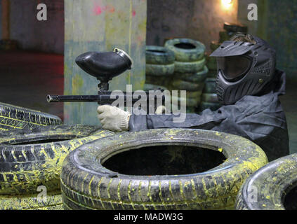 A man with a marker for paintball in the woods sitting for tires in the ambush. - Stock Photo