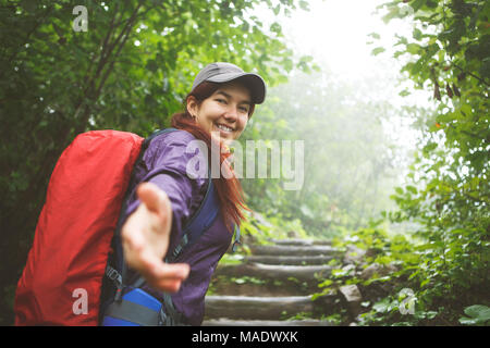 Photo of smiling woman in sports clothes with outstretched hand at forest in fall - Stock Photo