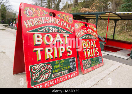 Sign advertising horse drawn narrowboat rides from the old wharfalong the 200 year old Llangollen canal in North Wales - Stock Photo