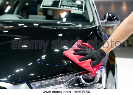 Car detailing - the man holds the microfiber in hand and polishes the car. Selective focus. - Stock Photo