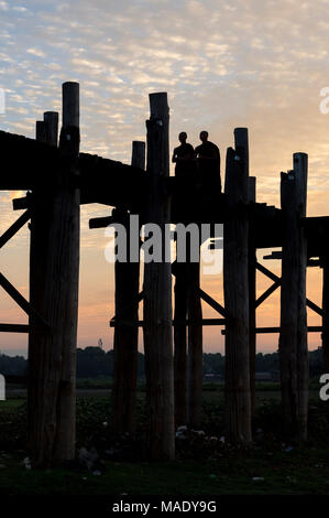 Buddhist monks walk on the U Bein Bridge at sunrise, Amarapura, Mandalay, Burma (Myanmar) - Stock Photo