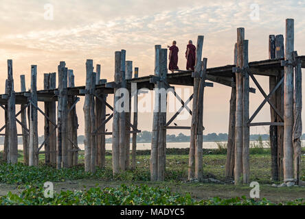 Buddhist monks walk on the U Bein Bridge in Amarapura near Mandalay, Burma (Myanmar) - Stock Photo