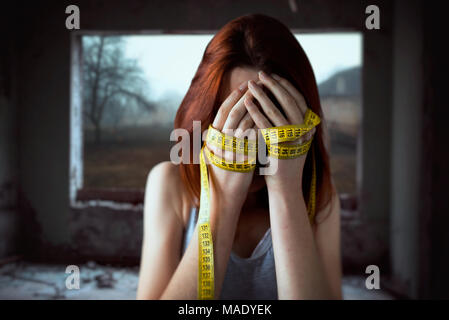 Woman covers face, hands tied with measuring tape - Stock Photo