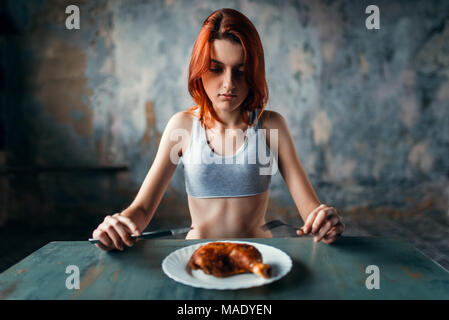 Woman against plate with food, absence of appetite - Stock Photo