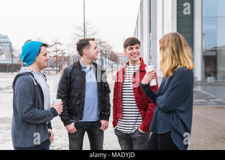 group of young adult friends having a conversation while standing together on city street - Stock Photo