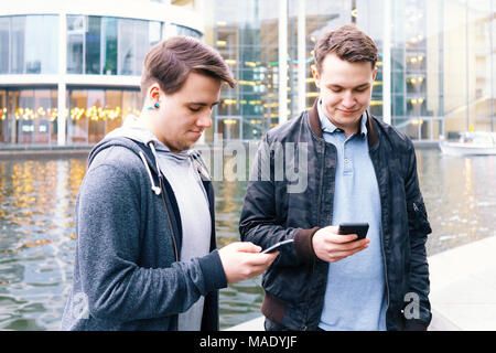 two mobile phone addicted male teenagers standing together looking at smartphone - Stock Photo