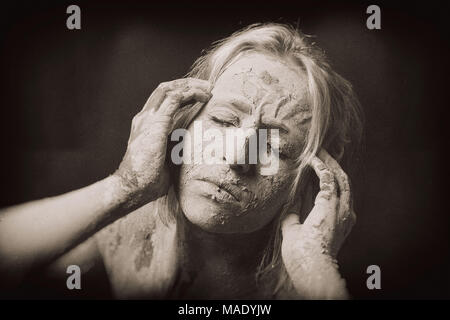 woman covered in dry cracked clay mask holding her head - Stock Photo
