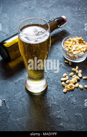 Lager beer glass and Peanuts on stone table. - Stock Photo