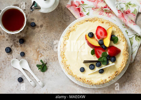 Delicious dessert cake with fresh berries and whipped cream, sweet delicious holiday cake with blueberries and strawberries on stone background. - Stock Photo