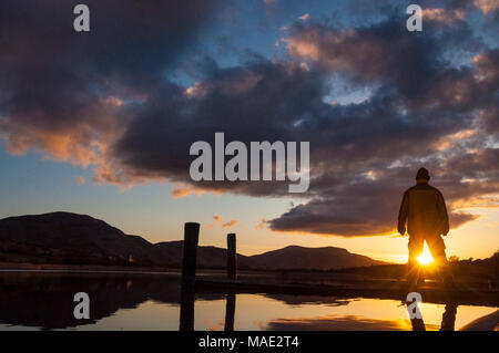 Ardara, County Donegal, Ireland weather. March 31st 2018. A man watches the sunset over Lake Shanaghan on the west coast. Photo by : Richard Wayman - Stock Photo