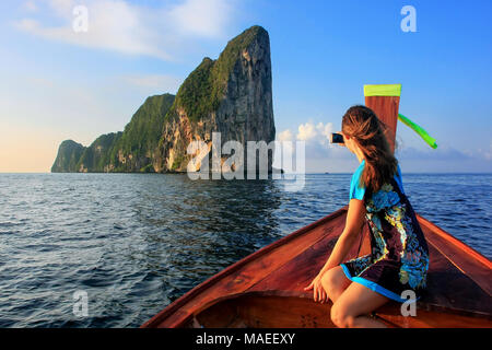 Young woman sitting in the front of a longtail boat going to Phi Phi Leh Island, Krabi Province, Thailand. Koh Phi Phi Leh is part of Mu Ko Phi Phi Na - Stock Photo