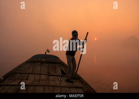Local man moving boat on Yamuna River with a pole at sunrise, Agra, Uttar Pradesh, India. Agra is one of the most populous cities in Uttar Pradesh - Stock Photo
