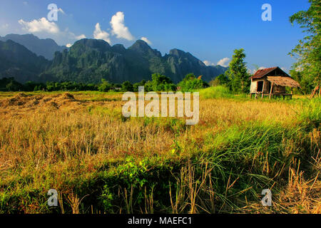 Farmer's hut on a field in Vang Vieng, Laos. Vang Vieng is a popular destination for adventure tourism in a limestone karst landscape. - Stock Photo