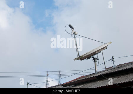 Modern high technology satellite on a roof with cloudy sky - Stock Photo