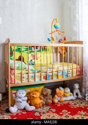 Baby crib in the children's room with toys - Stock Photo