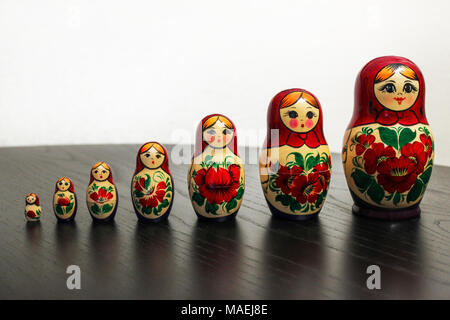Russian nesting dolls in a row on a black wooden table - Stock Photo