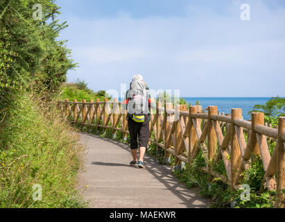 Lonely Pilgrim with backpack walking the Camino de Santiago in Spain, Way of St James - Stock Photo