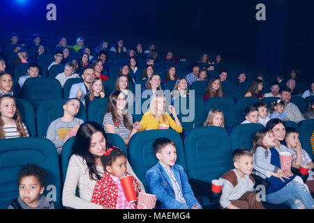 frontview of young exited people watching interesting movie in cinema hall. Boys and girls look very emotional and happy. Models wearing colorful clothes,eating popcorn, drinking fizzy drinks. - Stock Photo