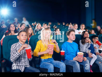 frontview of little exited children watching interesting movie in cinema hall. Boys and girls look very emotional and happy. schoolmates wearing colorful clothes,eating popcorn, drinking fizzy drinks. - Stock Photo