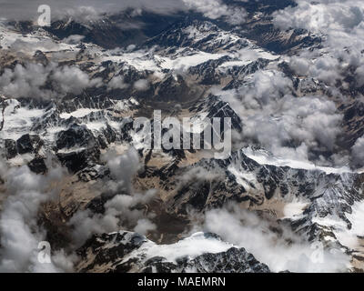 Mountain chains, a photograph from a great height: brown mountains, peaks covered with white glacier snows, numerous thin cumulus clouds. - Stock Photo