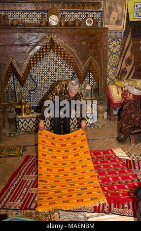 Morocco, Fes, Fes el Bali, Medina, antiques shop, salesman displaying colourful carpets - Stock Photo