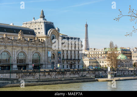 Paris, France - March 14, 2018: View of the facade of the former Orsay train station which houses the Orsay museum since 1986, with the Eiffel tower i - Stock Photo