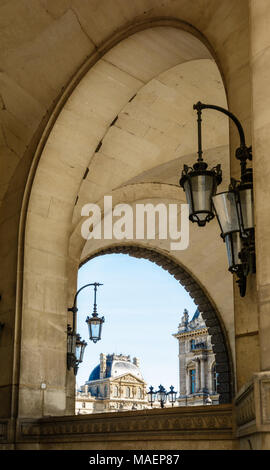Paris, France - March 14, 2018: View of the Richelieu pavilion of the Louvre palace in Paris from the arches of the Guichets Lesdiguieres with vintage - Stock Photo