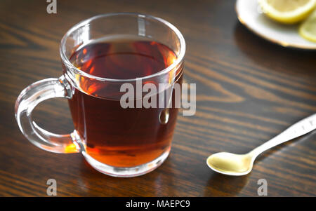 On the surface of the table in a glass Cup hot strong tea and lemon. - Stock Photo
