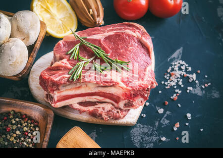Cuts of beef for grilling on a wooden cutting Board with the Bay leaf, rosemary, olive oil and Provencal herbs for the marinade in a rustic style. - Stock Photo
