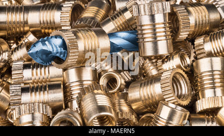 Bronze thread inserts and spiral flute tap. Detail of shiny metallic nut heap and cutter tool for threading. Machining, build, metalwork, engineering. - Stock Photo
