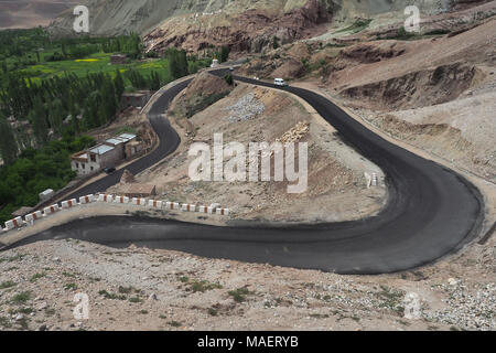 Mountain road among the brown rocks: the gray roadway curves in circles, on the left bright summer greens. - Stock Photo