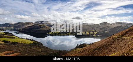 Panoramic view of Ullswater from the side of Gowbarrow Fell with the sky reflected in the calm lake - Stock Photo