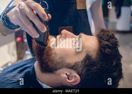 Close-up of the head of a man and the hand of a barber trimming  - Stock Photo
