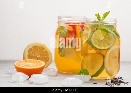 Fruit ice tea and ginger herbal ice tea with mint in glass jars, white background, copy space. Summer refreshing drink concept. - Stock Photo