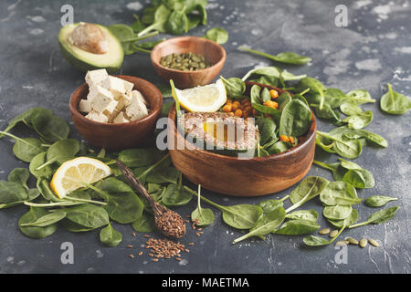 Healthy vegetarian salad with tofu, chickpeas, avocado and sunflower seeds. Healthy vegan food concept. Dark background, copy space. - Stock Photo
