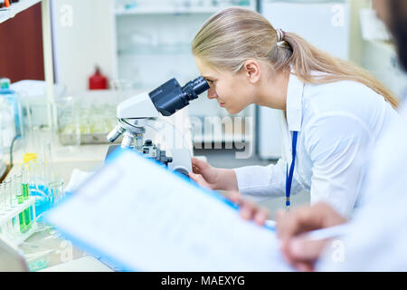 Serious medical student analyzing sample through microscope - Stock Photo