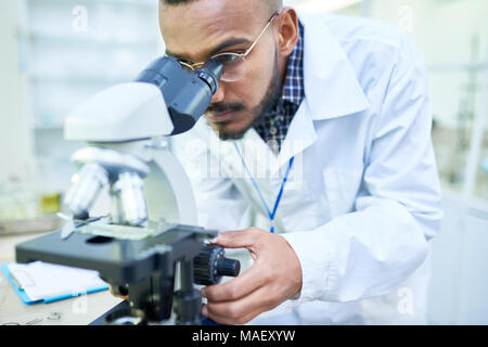 Modern handsome biologist adjusting microscope to zoom image - Stock Photo