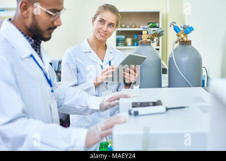 Smiling female assistant asking doctor of medicine - Stock Photo