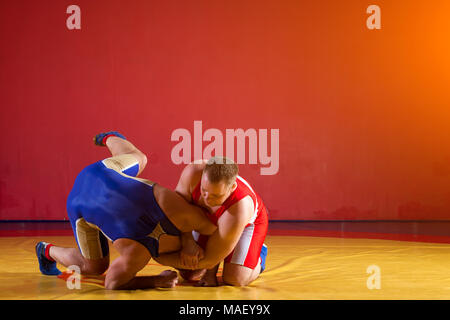 Two greco-roman  wrestlers in red and blue uniform wrestling   on a yellow wrestling carpet in the gym - Stock Photo