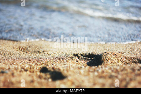 Footprints on wet sand leading to the sea, close-up - Stock Photo
