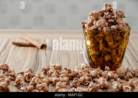 chocolate flavored popcorn in yellow glass and on the brown wood table with cinnamon background - Stock Photo