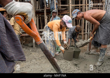 Construction workers on a building site. Lashio, Shan State, Myanmar - Stock Photo