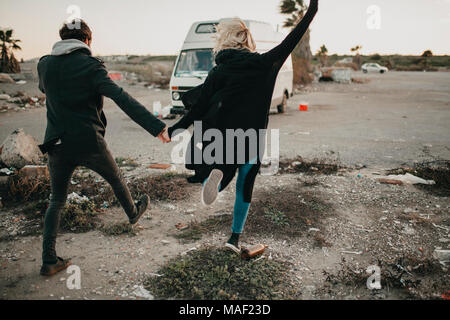 Young couple walking on their back in a deserted place with an auto van in the background. - Stock Photo