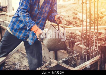 mason or plasterer pour construction cement on floor. - Stock Photo