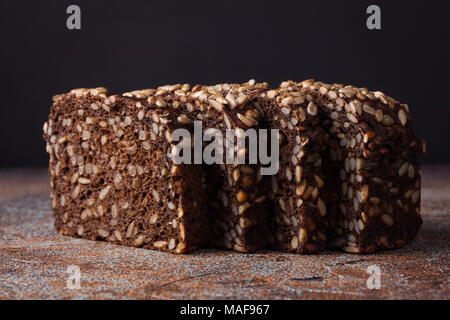 Fresh black bread with sunflower seeds on an old rusty table. - Stock Photo
